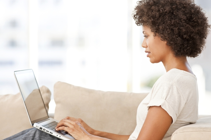 Woman typing on her laptop while sitting on her couch.